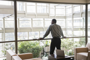 Black businessman leaning on window