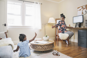 African American mother and daughter gesturing thumbs up