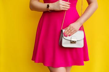Wall Mural - Fashion girl in pink dress with silver handbag