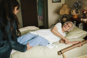 Granddaughter helping grandmother into bed