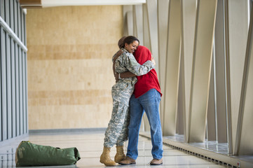 African American soldier hugging husband in airport
