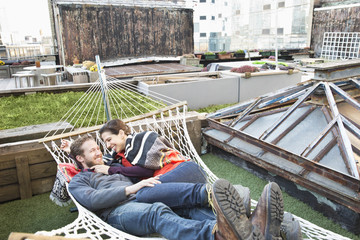 Couple laying in hammock on urban rooftop