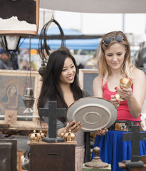 Friends looking at items in flea market