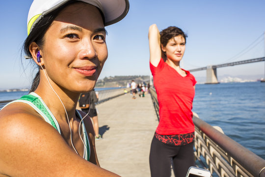 Runner stretching on urban footbridge, San Francisco, California, United States