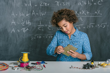 Mixed race student building vehicle in science class