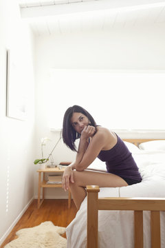Hispanic woman sitting on bed