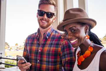 Smiling couple using cell phone together