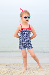Charming little girl in a bathing suit and sunglasses posing on