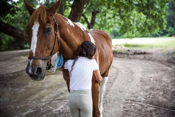 Teenage girl hugging horse in field