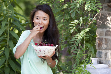 Woman eating grapes in garden