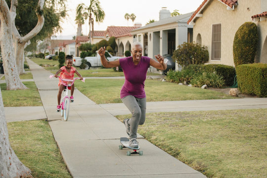 Grandmother and granddaughter skateboarding and riding bicycle