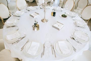 Elegant wedding reception white table arrangement restaurant,  candlestick on table. Plates, forks and glasses