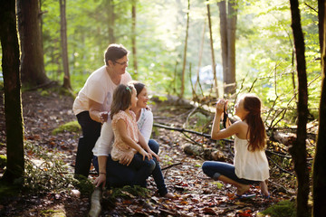 Caucasian girl photographing family in forest