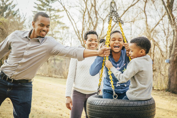 Black family playing on tire swing