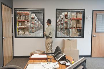Hispanic man standing in warehouse office