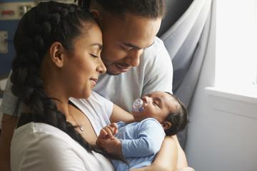 Couple cradling newborn baby