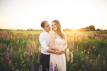 Emotional beautiful bride hugging newlywed groom from behind sunset at a field closeup