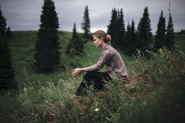 Side view of woman sitting on a meadow