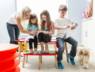 Caucasian family drawing at table in playroom