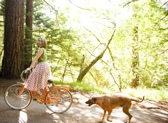 Mixed race woman riding bicycle with dog