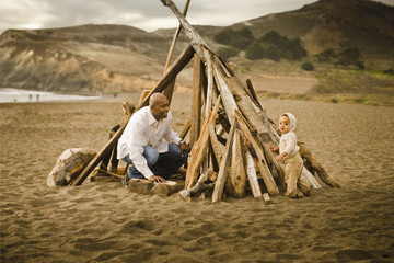 Father and baby son sitting under driftwood teepee on beach
