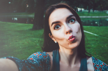 Pretty girl taking photo selfie and making duck face. Female sending kisses, enjoying self portrait. Herself Instagram concept. Lifestyle  of happy woman looking on camera phone.