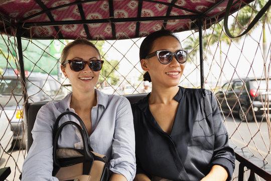Businesswomen riding in tuk tuk taxi
