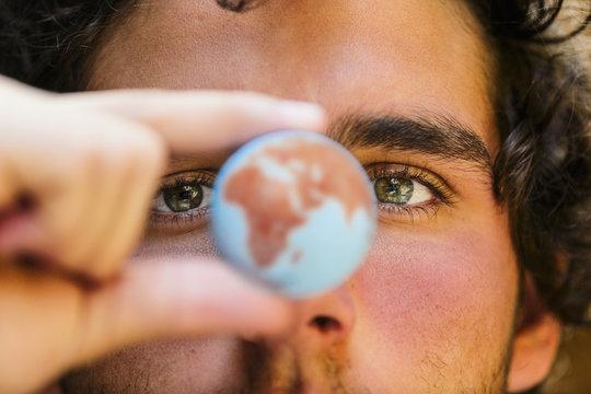 Close up of Hispanic man holding miniature globe