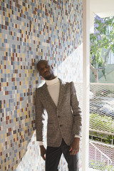 African man in tweed jacket leaning against tiled wall