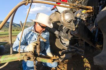 Hispanic farmer working on tractor