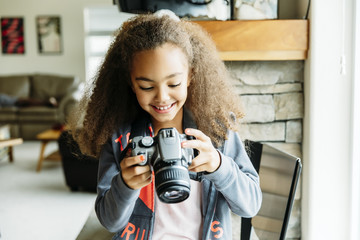 Smiling girl holding camera while sitting on chair