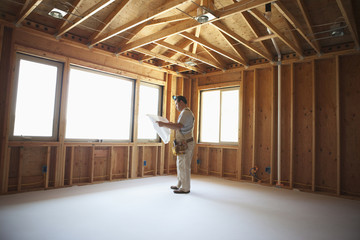 Hispanic construction worker looking at blueprints in unfinished room