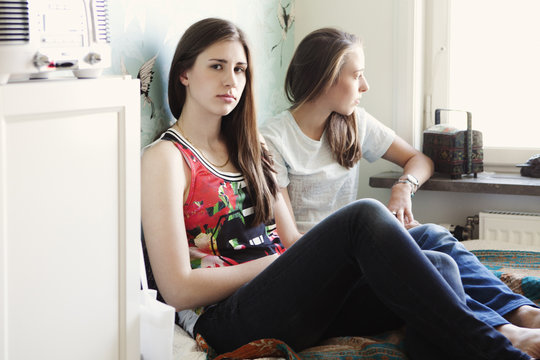 Serious sisters sitting on bed