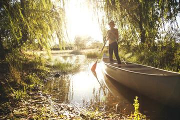 Caucasian woman rowing canoe in rural creek