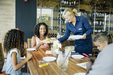 Waitress serving food to family in the restaurant