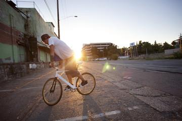 Man doing stunts on bicycle on city street
