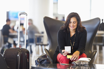 Hispanic businesswoman using cell phone in airport waiting area
