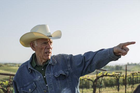 Hispanic farmer pointing in vineyard