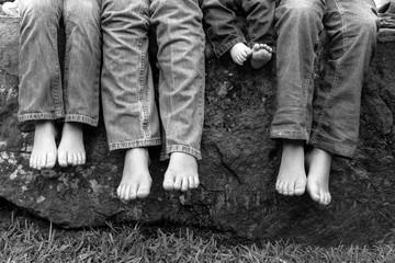 Legs and feet of siblings sitting on rock