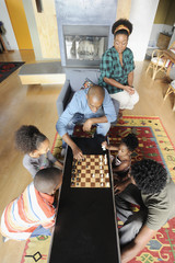 Black family watching chess game