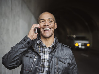 Black man talking on cell phone in urban tunnel
