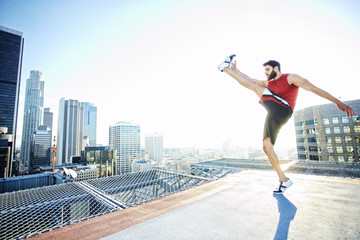 Caucasian man kicking on urban rooftop