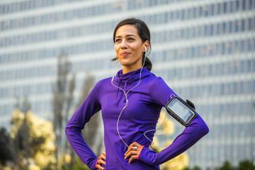 Hispanic runner standing near high rise building