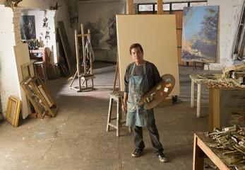 Hispanic artist standing in studio