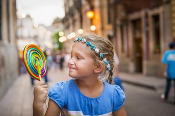 Smiling Caucasian girl enjoying lollipop in city