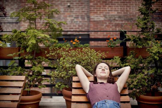 Teenage girl relaxing on urban rooftop