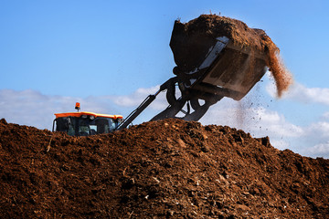 Excavator shovel working on a large heap of manure, organic fertilizer