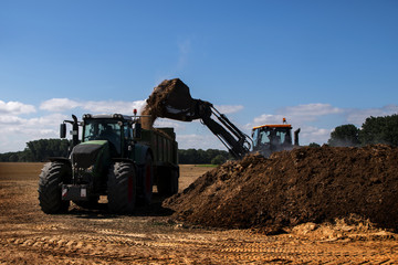 fertilize the field, excavator with shovel fills manure in the ttraile of a tractor