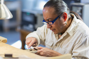 Close up of Native American jeweler working in studio