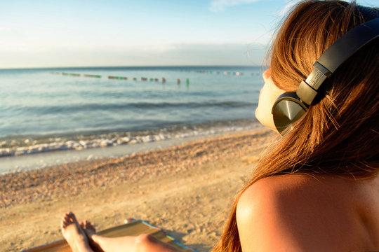 Beautiful young girl in bikini is listening music with headphones on the beach